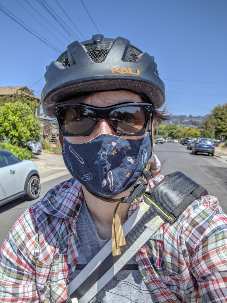 Selfie of me wearing a bike helmet, sunglasses, and mask in the middle of the street.